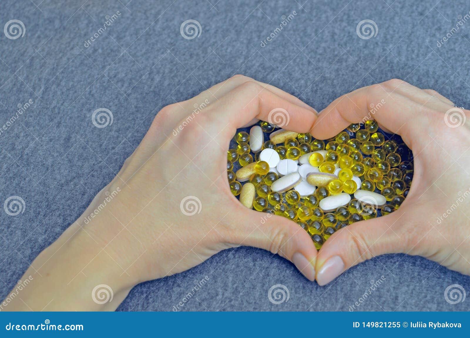 妇女的手创造了一心形 白色和黄色药片 假装为特价作为广告 医疗和