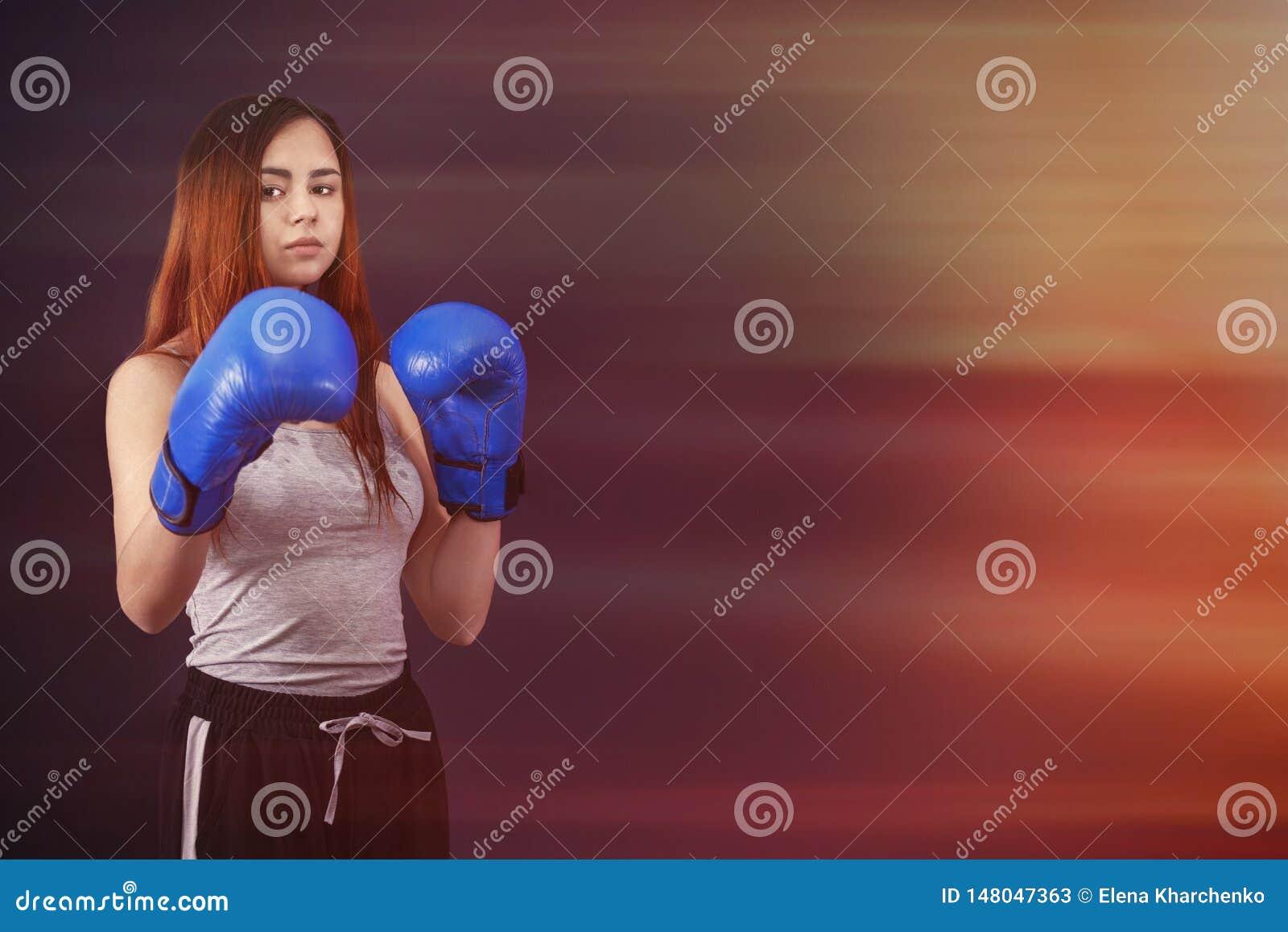 妇女的把装箱的女孩拳击手在拳击手套站立