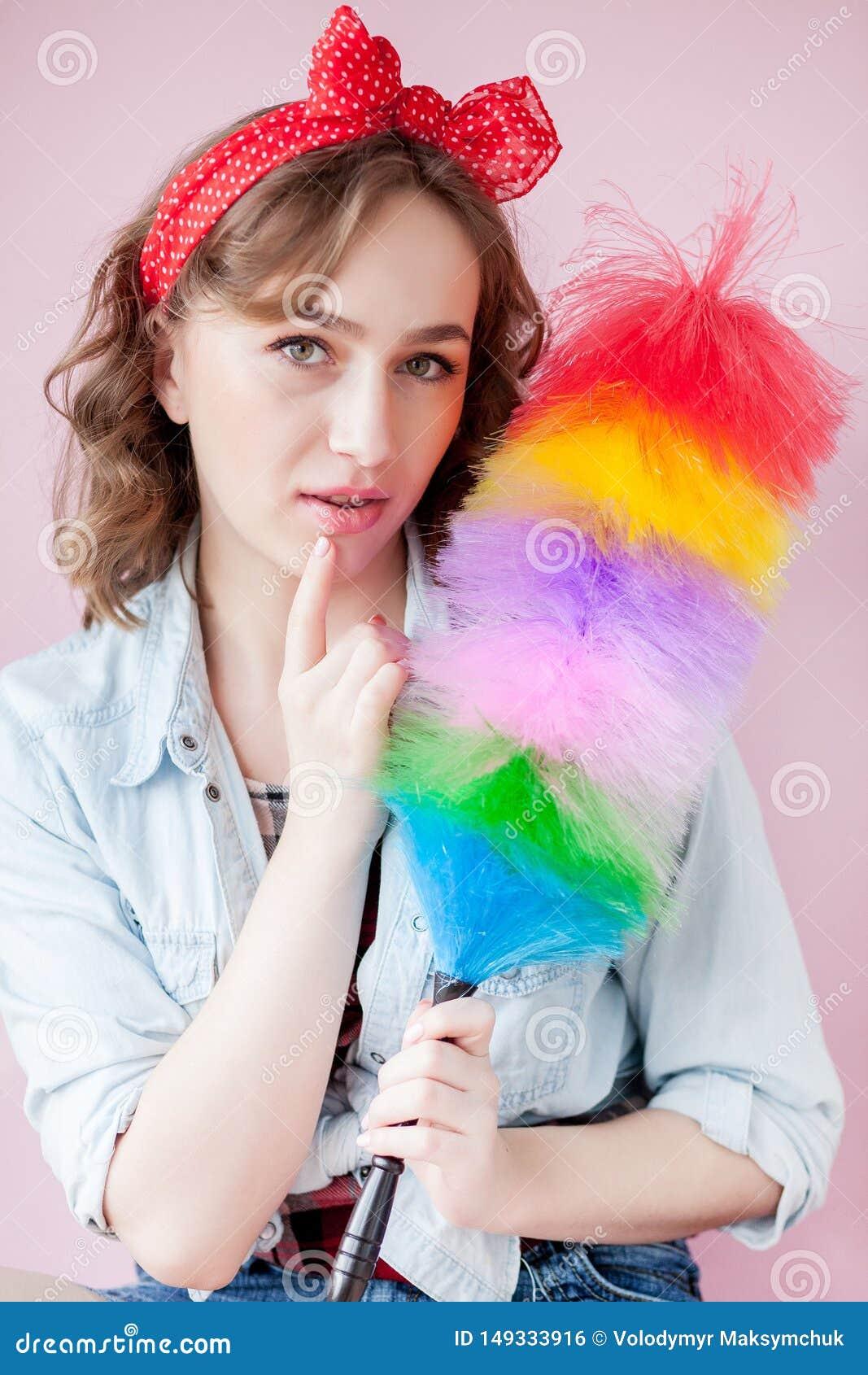 妇女的清洗的别针 微笑的画报女孩拿着五颜六色的喷粉器刷子 r 画报与羽毛喷粉器的女孩擦净剂