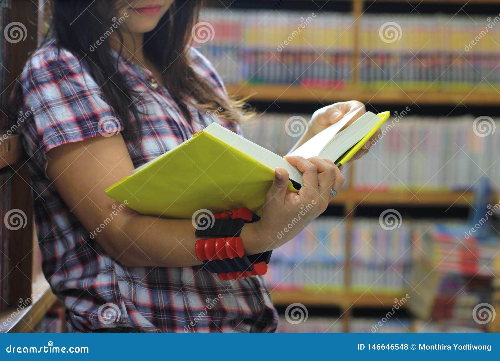 妇女看书在图书馆屋子和书架背景,教育概念里