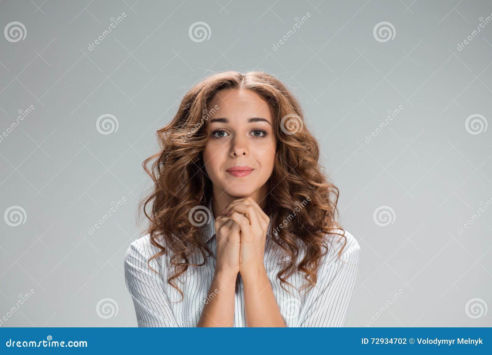妇女看起来祈求在灰色背景