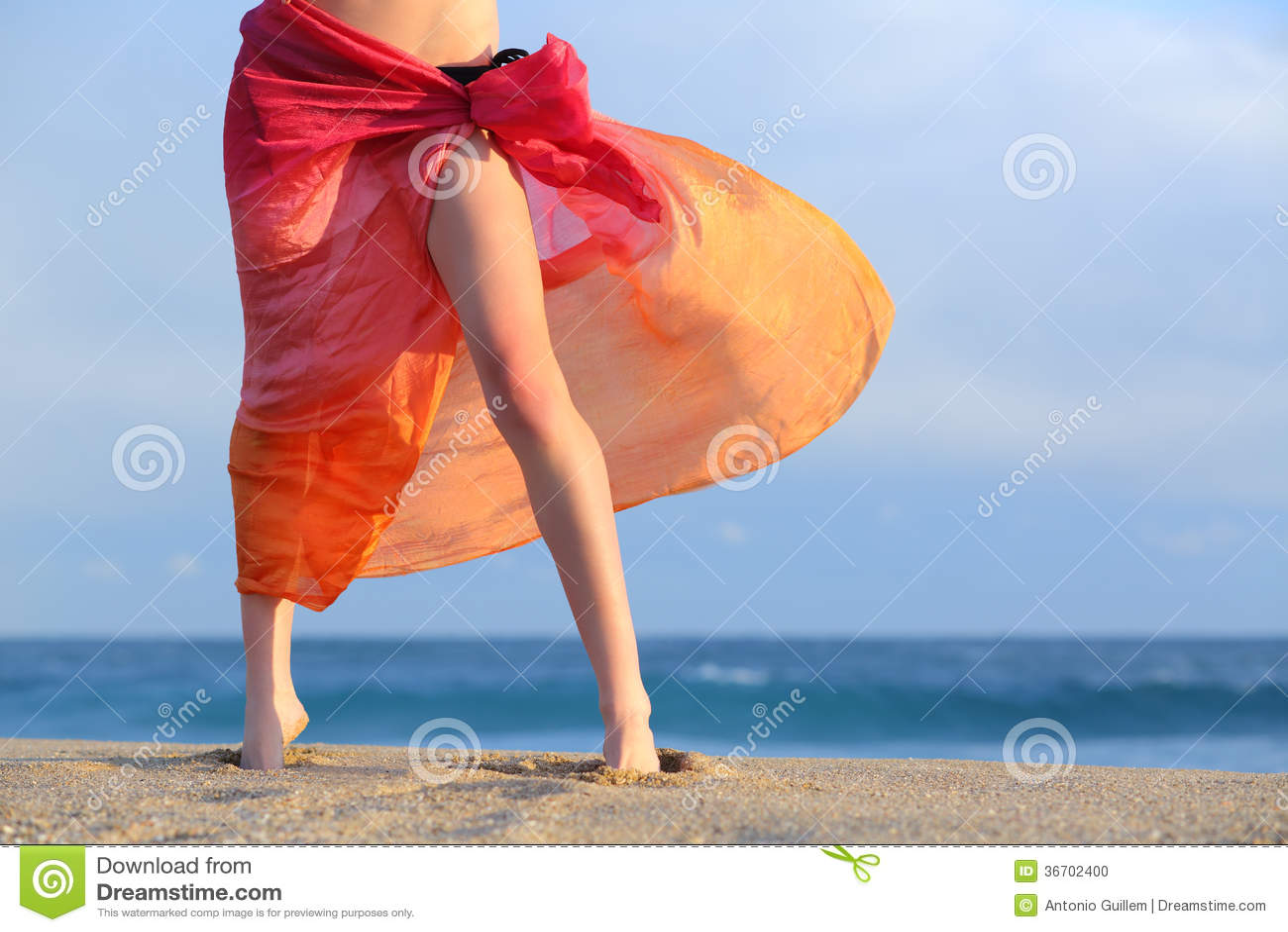 妇女腿在度假摆在与pareo的海滩的