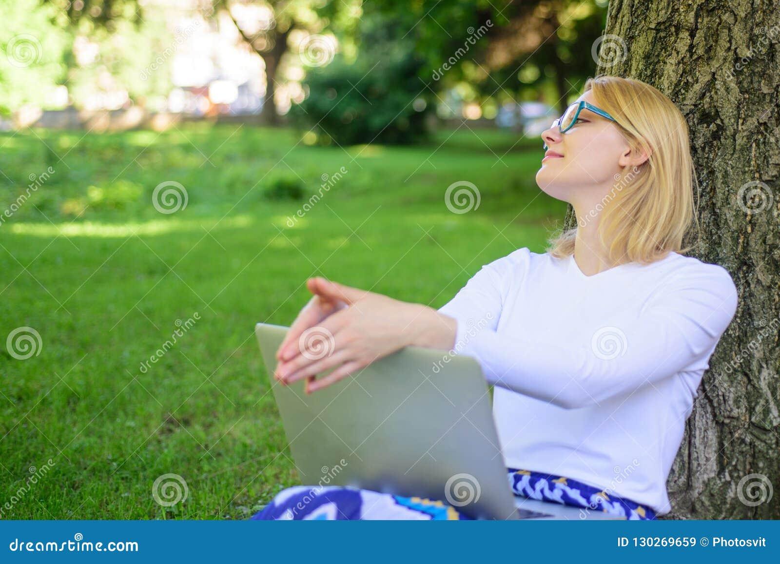 妇女膝上型计算机在网上公园研究 女孩坐与笔记本的草 女孩作为好处真正教育 需要分钟发现