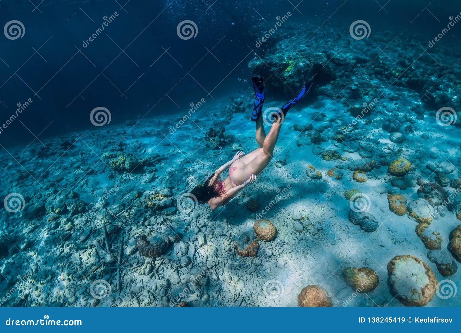 妇女自由潜水者游泳在水面下在热带海洋
