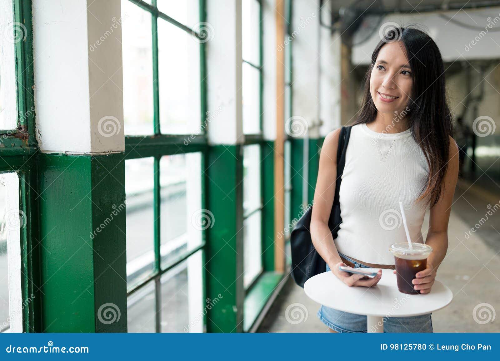 妇女藏品冰了咖啡和看在窗口外面