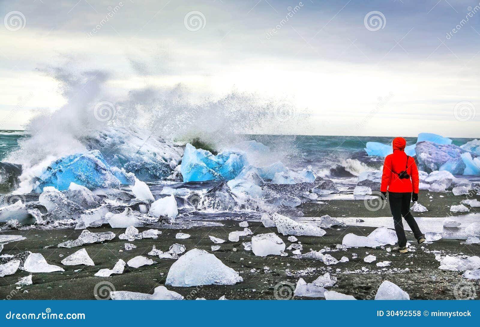 妇女观看的波浪碰撞反对冰山在Jokulsarlon冰河盐水湖在Vatnajokull国家公园,东南冰岛附近