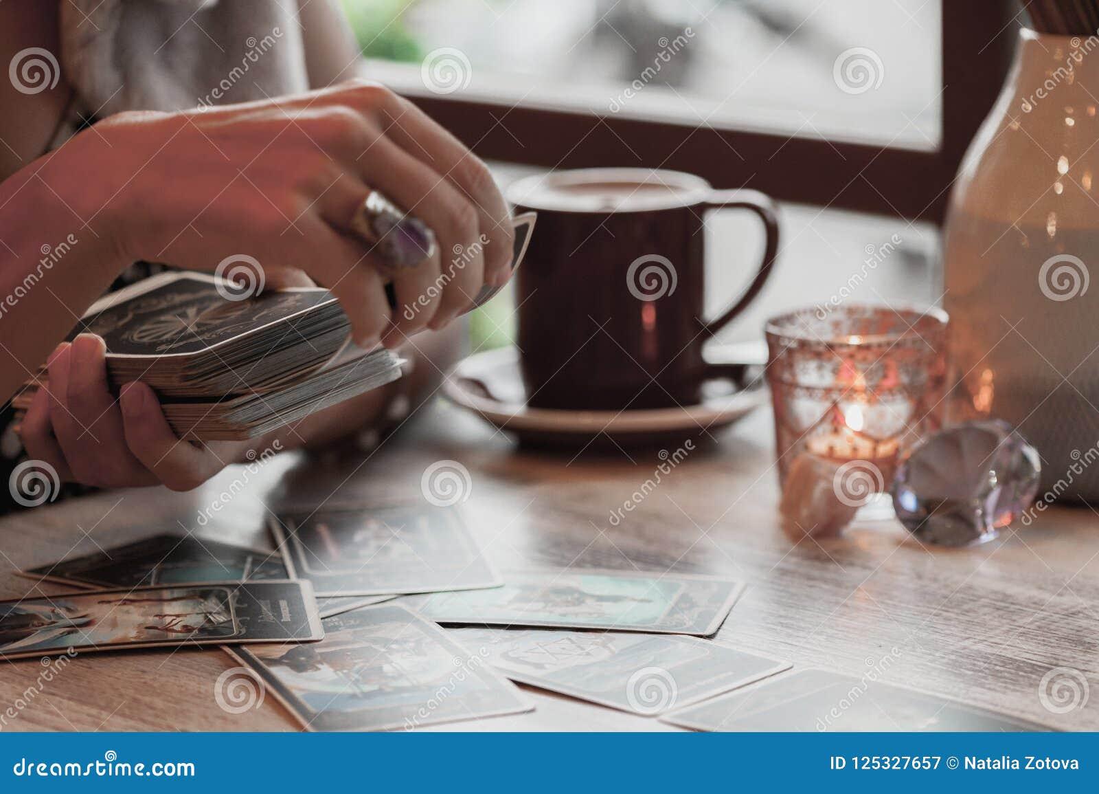 妇女读在咖啡馆的占卜用的纸牌