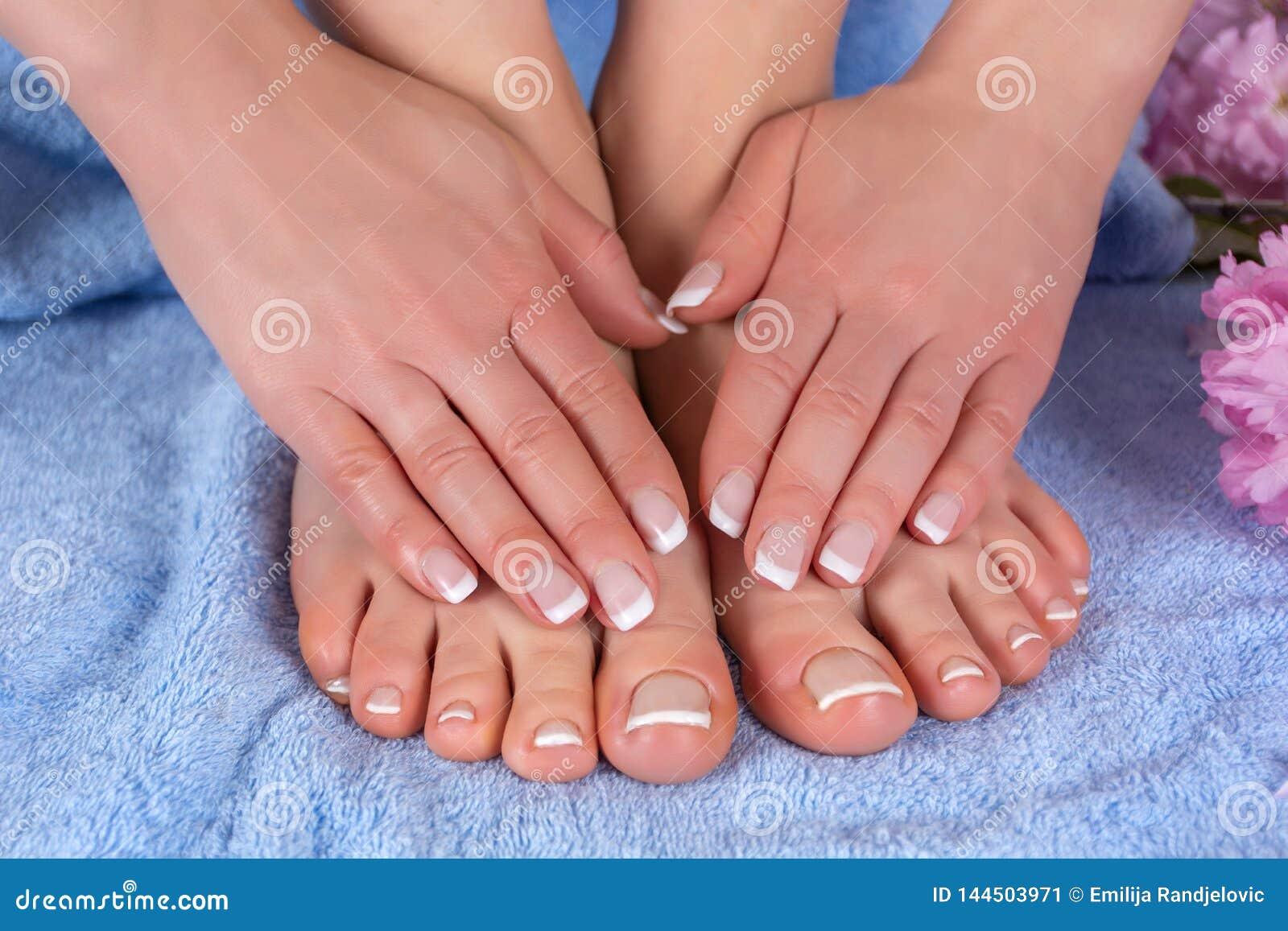 妇女赤脚和手有法国指甲油的在蓝色毛巾与桃红色花在演播室