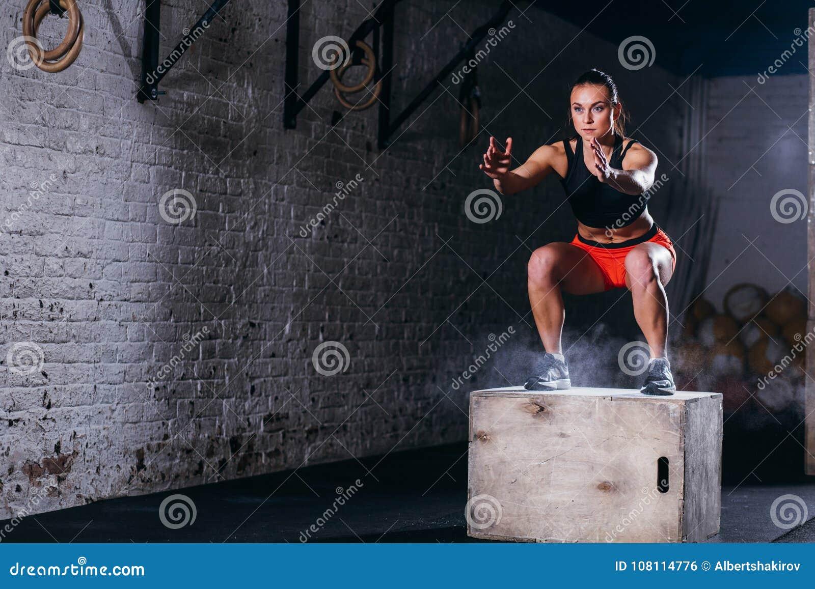 妇女跳跃的箱子 做箱子跃迁锻炼的健身妇女在十字架适合的健身房