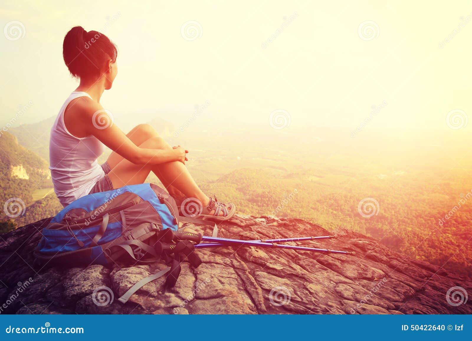 妇女远足者享受看法在山峰峭壁