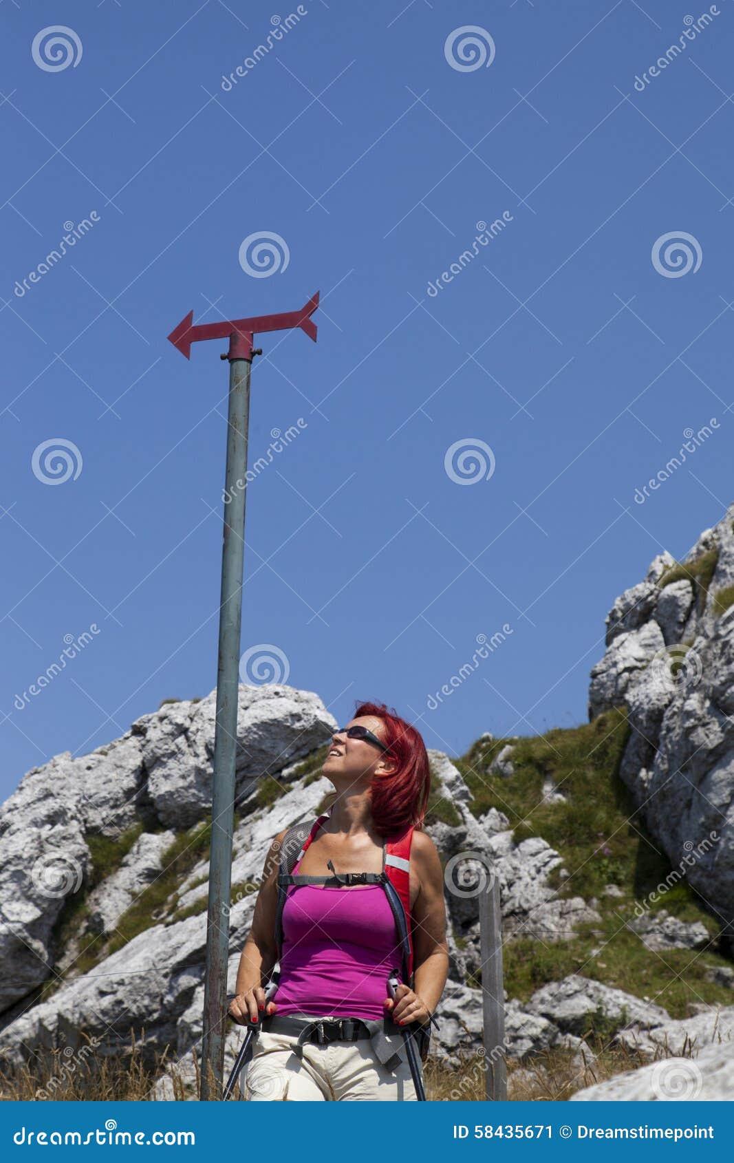 妇女远足者高在休息在路标下的山