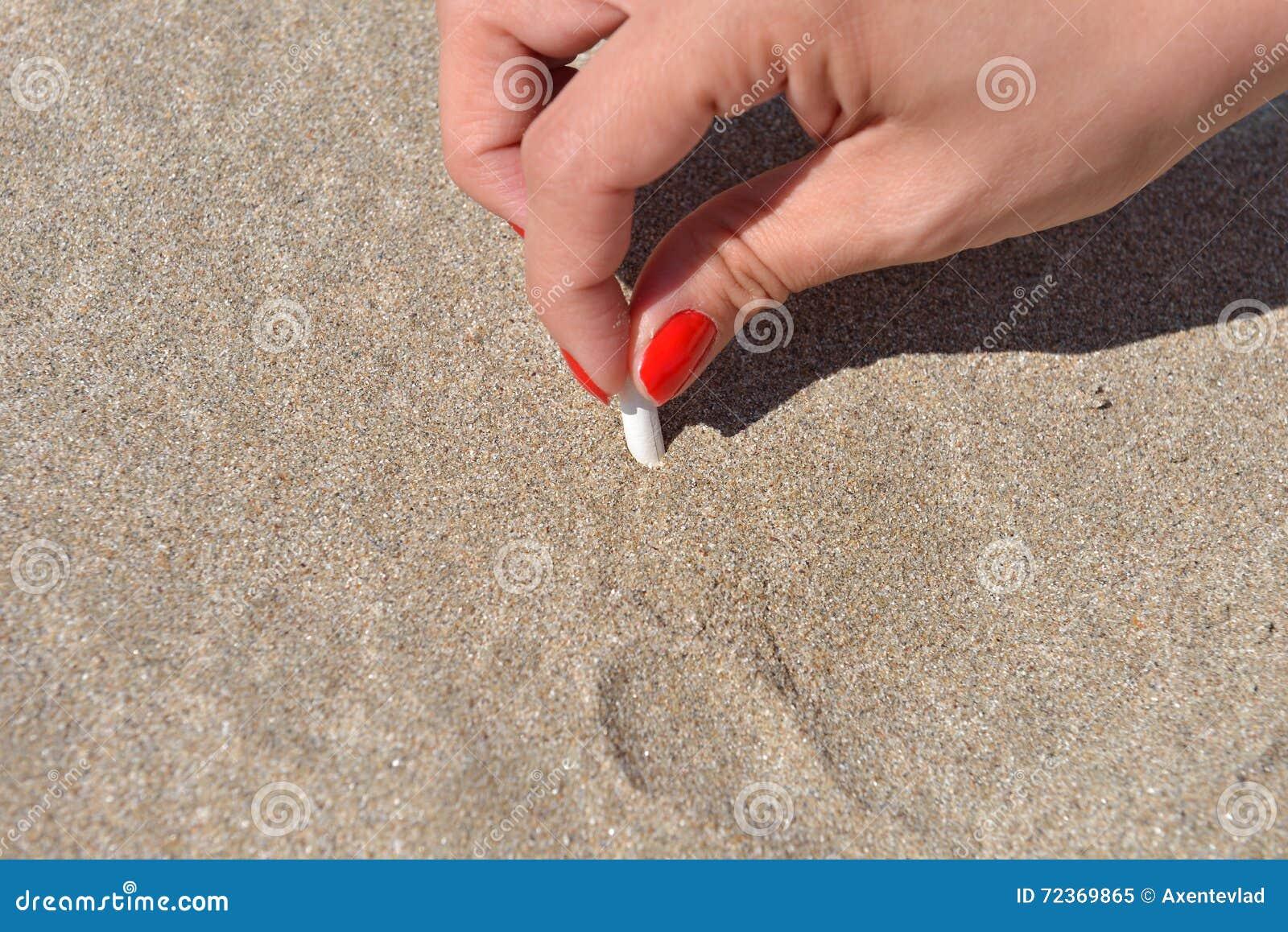 妇女递熄灭香烟入海滩的沙子 Quitti