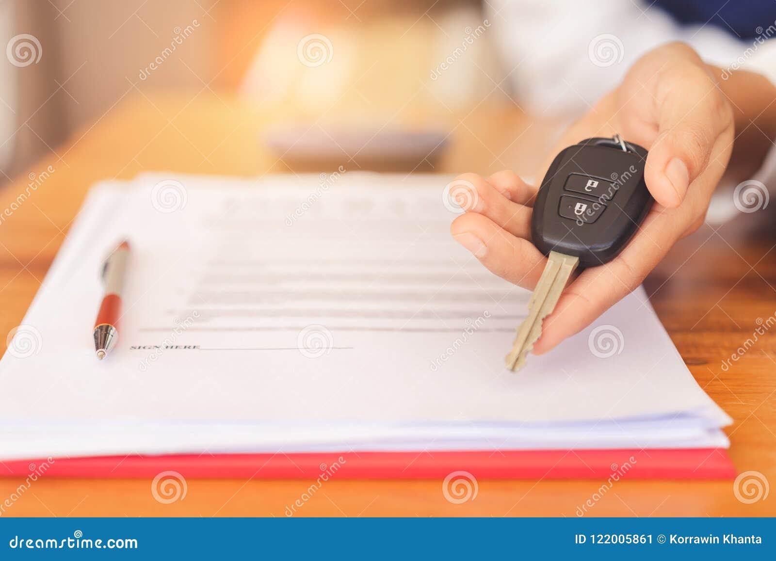 妇女递给汽车遥远的钥匙,在签字的合同约定和成功的成交后