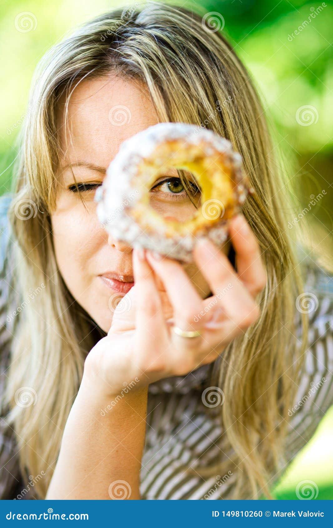 妇女通过在蛋糕Trdelnik的孔看