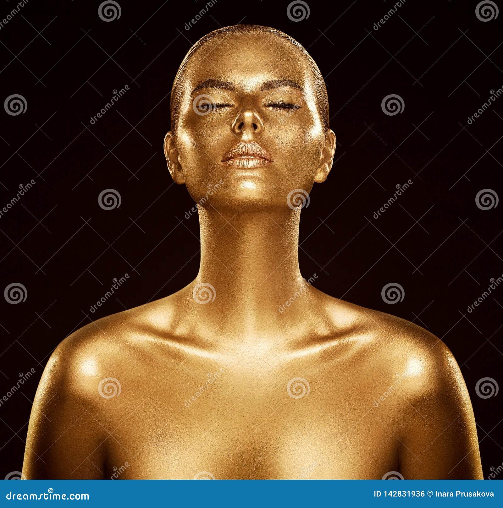 妇女金皮肤、时装模特儿金黄人体艺术、秀丽画象面孔和身体亮光作为金属