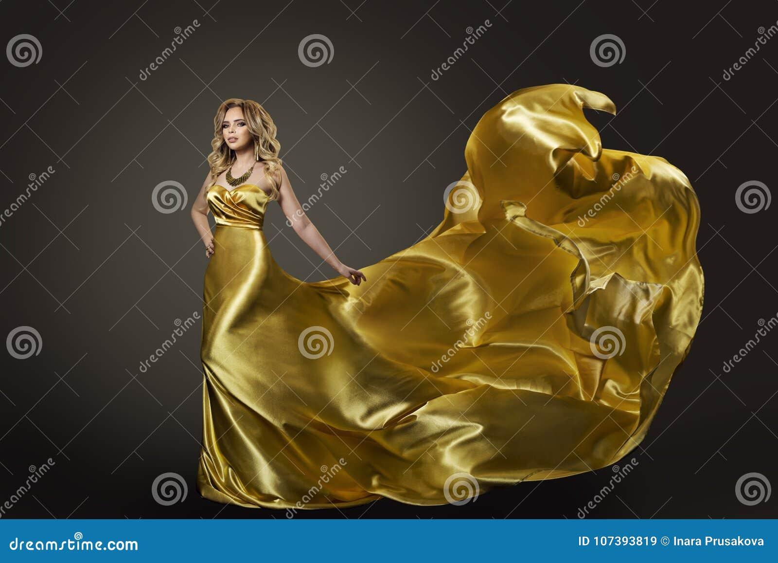 妇女金礼服,在长的丝绸褂子的时装模特儿跳舞