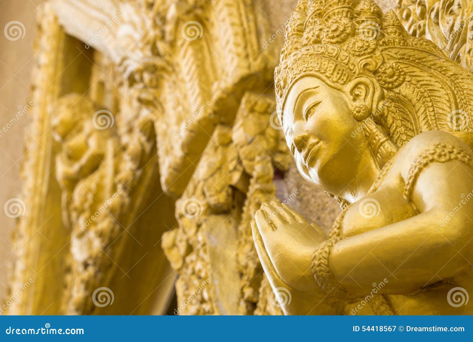 妇女金雕象在寺庙祈祷 Ubonratchathani泰国