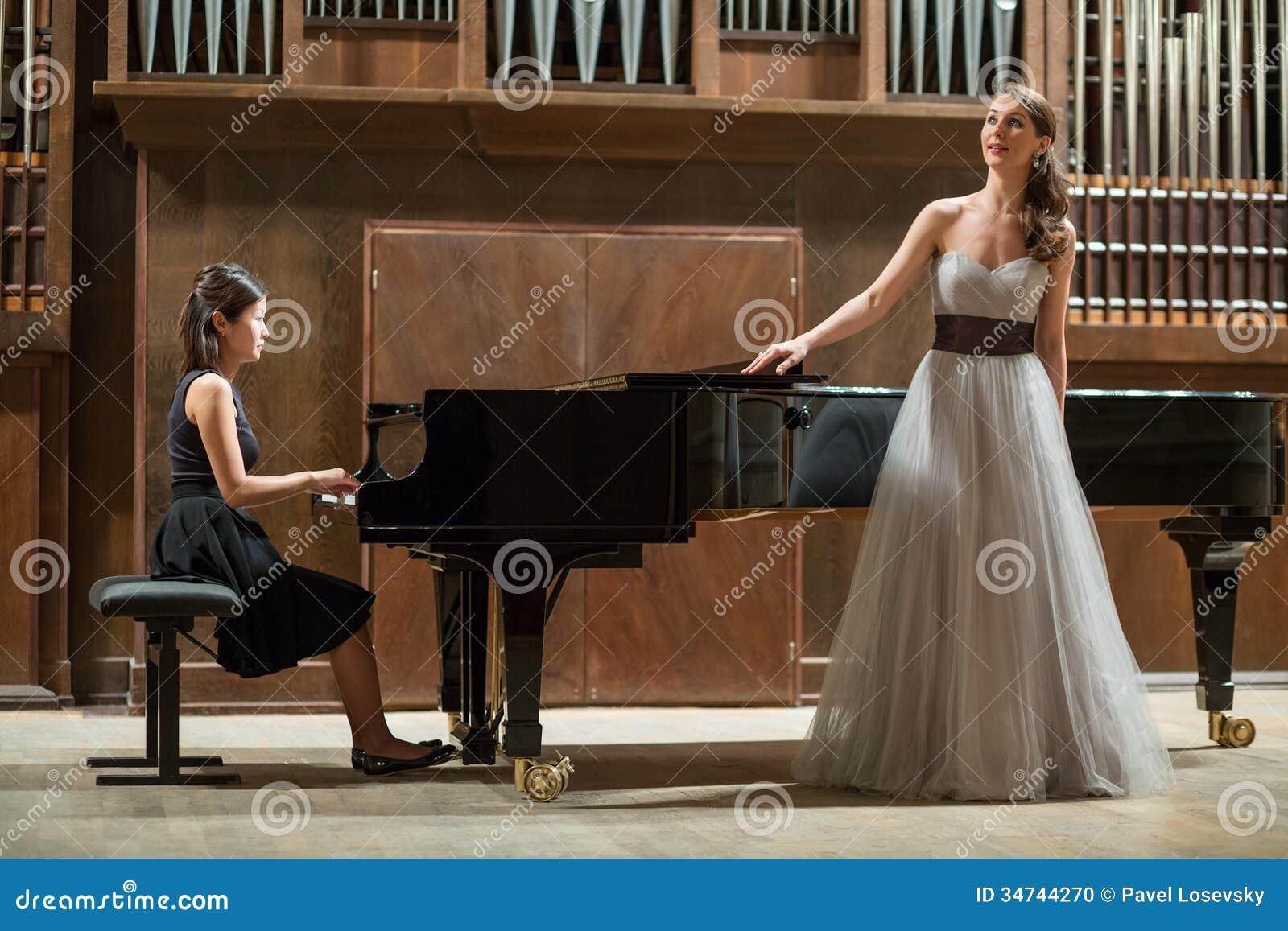 妇女钢琴演奏家扮演钢琴和美丽的歌手