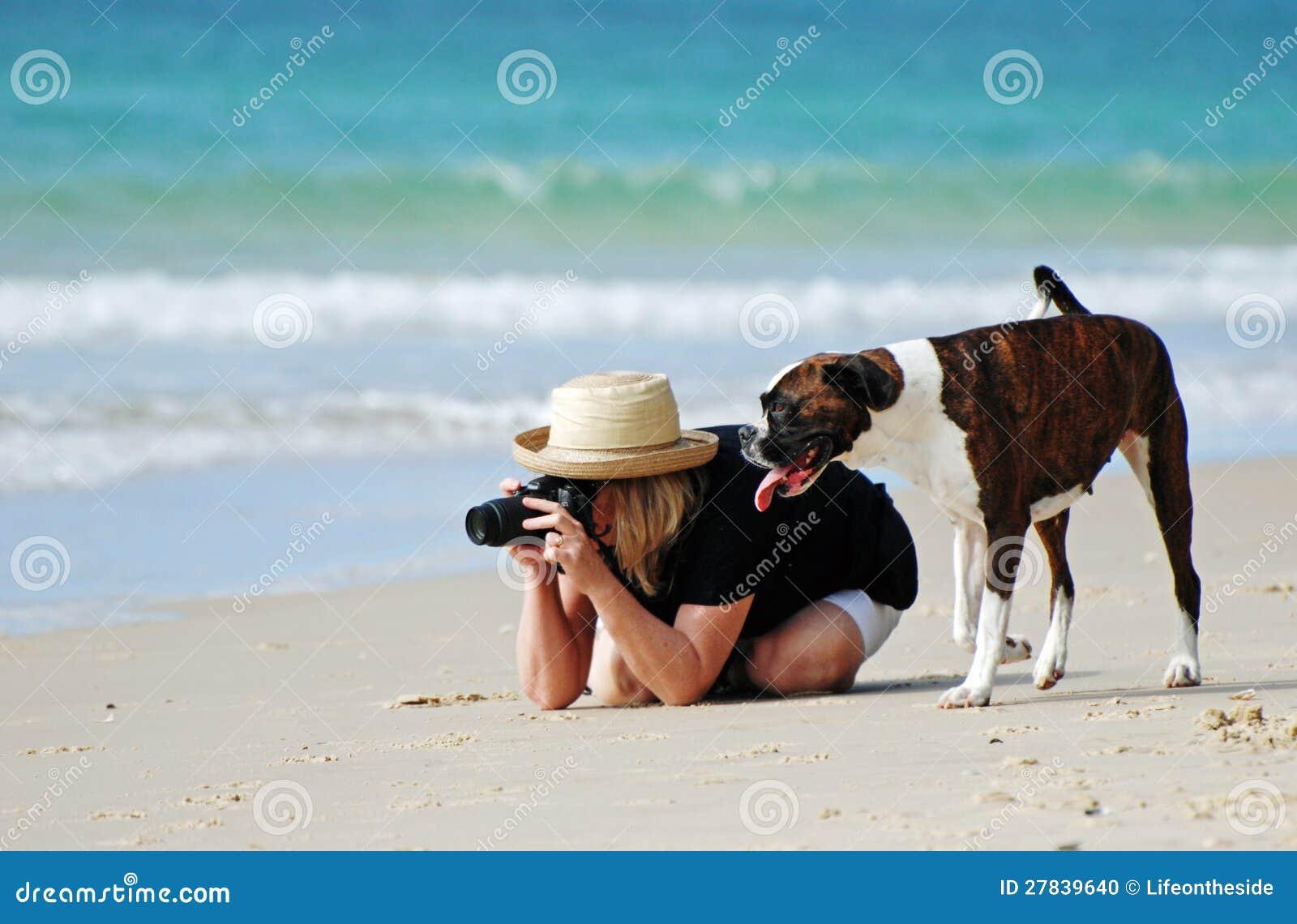 妇女&在采取照片的热带海滩的爱犬