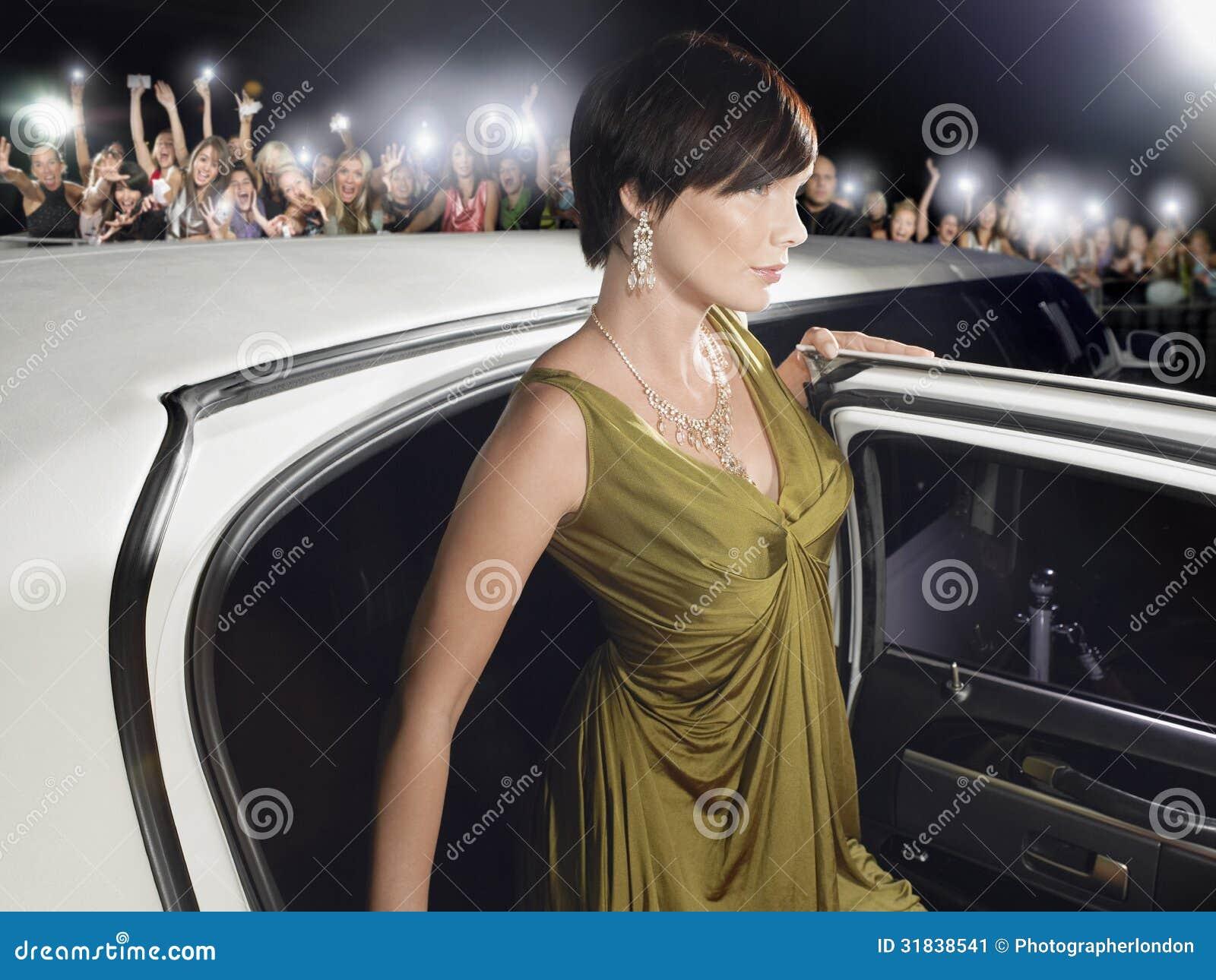 妇女离开在爱好者和无固定职业的摄影师前面的大型高级轿车