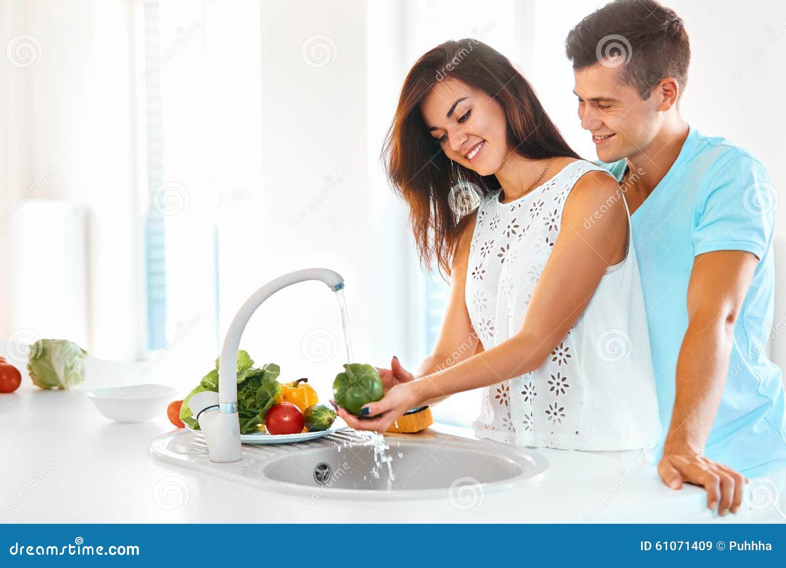 洗涤菜的愉快的年轻美丽的妇女,当拥抱她的英俊的人从后面在厨房里时.图片