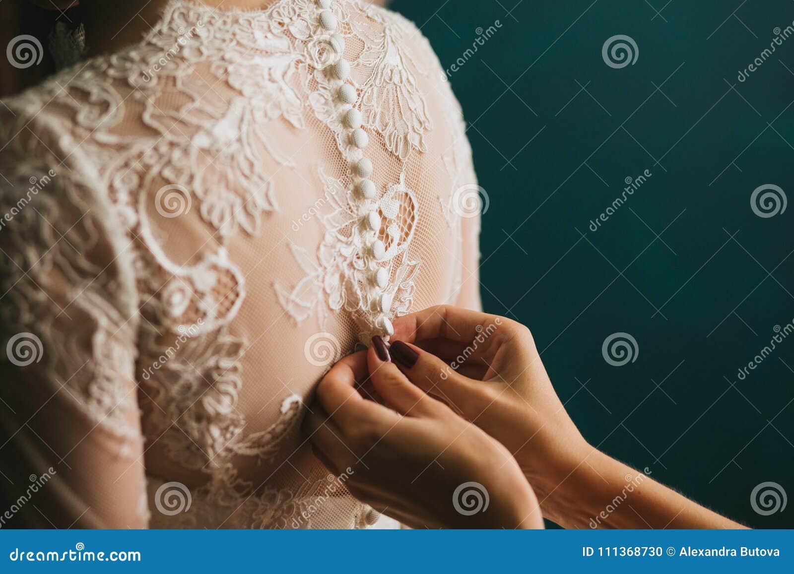 妇女` s手紧固与按钮在一个美丽的白色婚礼鞋带葡萄酒礼服特写镜头,早晨训练背面 turquo