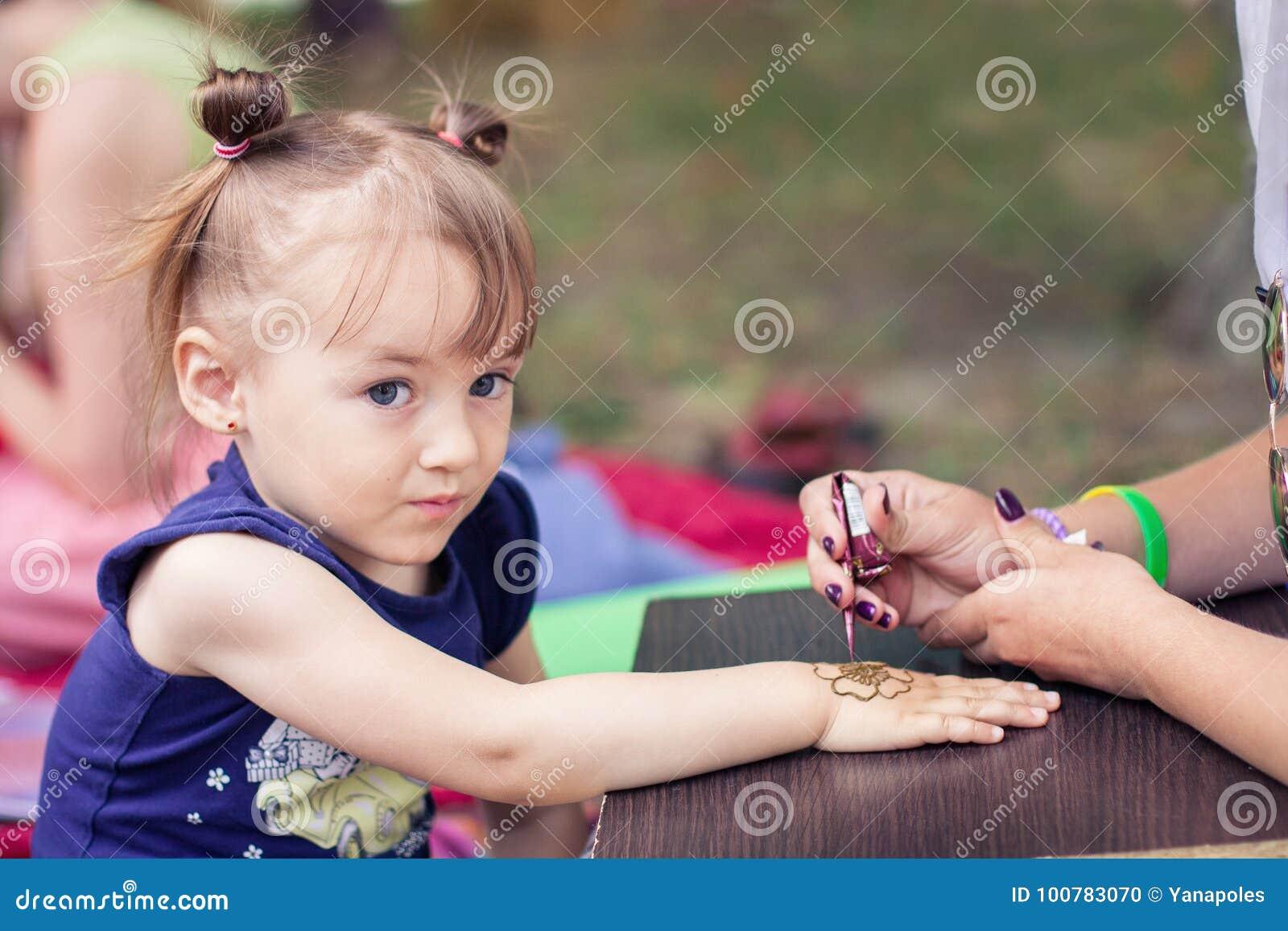 妇女mehendi艺术家在儿童` s手上的绘画无刺指甲花