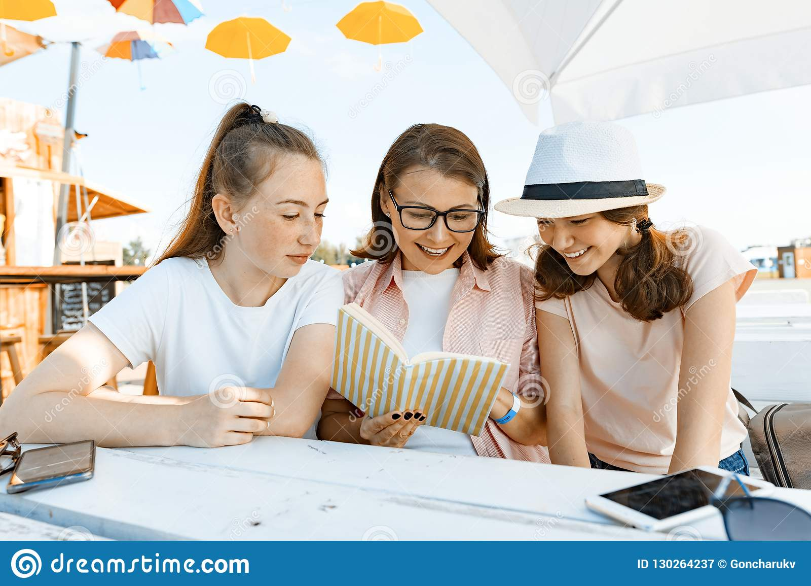 妈妈和女儿少年有乐趣,谈话,神色和读的有趣的书 青少年的父母和孩子的通信