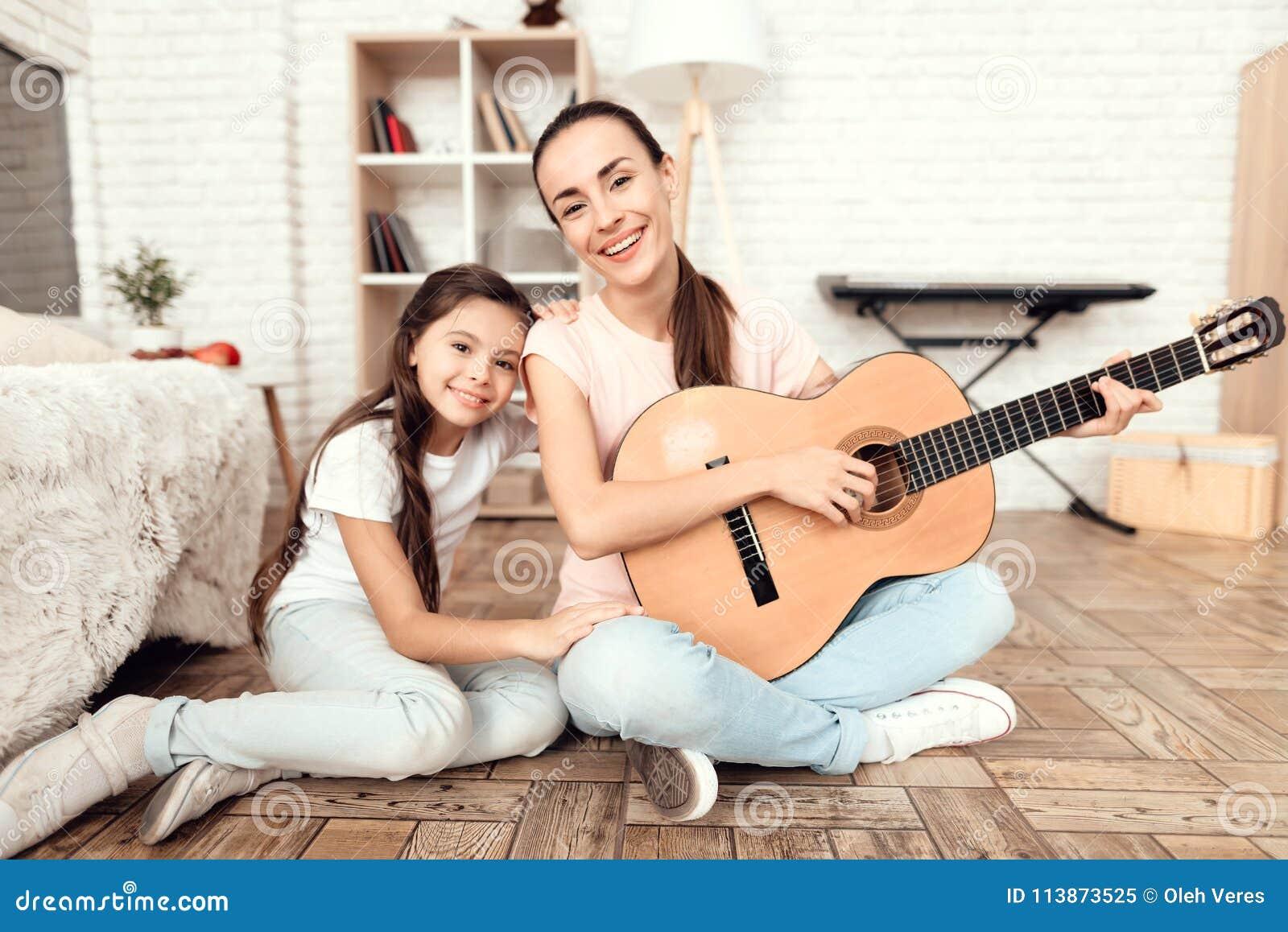 妈妈和她的女儿在家坐地板并且弹吉他 他们唱歌到吉他