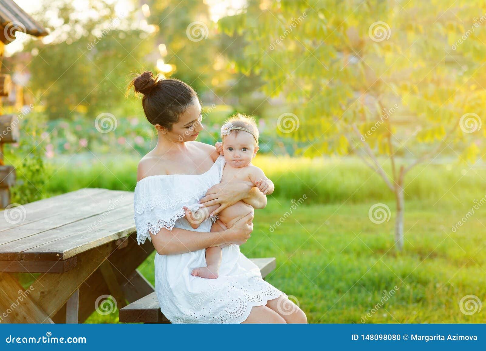 妈妈护理她的孩子本质上 幸福家庭坐日落背景