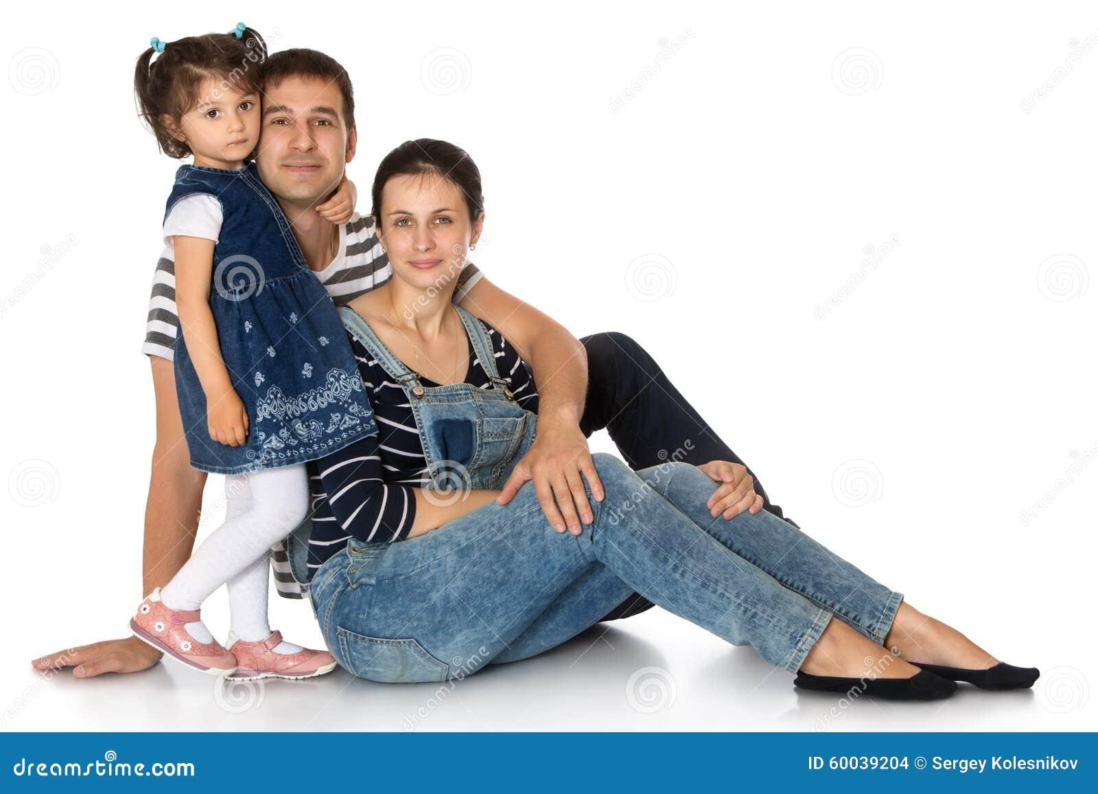 赵奕欢的爸爸妈妈_愉快的幼小三口之家 妈妈和爸爸坐地板,拥抱在白色背景女儿隔绝的他们
