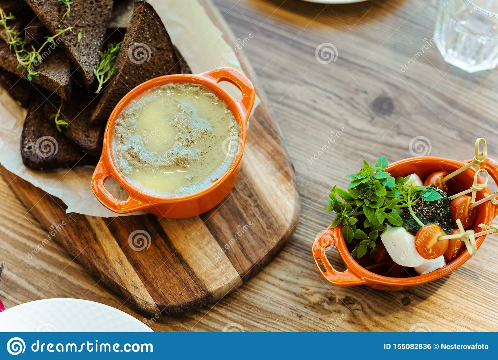 委员会用黑麦薄脆饼干用迷迭香、自创肝脏头脑和一块板材用乳酪,新鲜的西红柿和微绿色