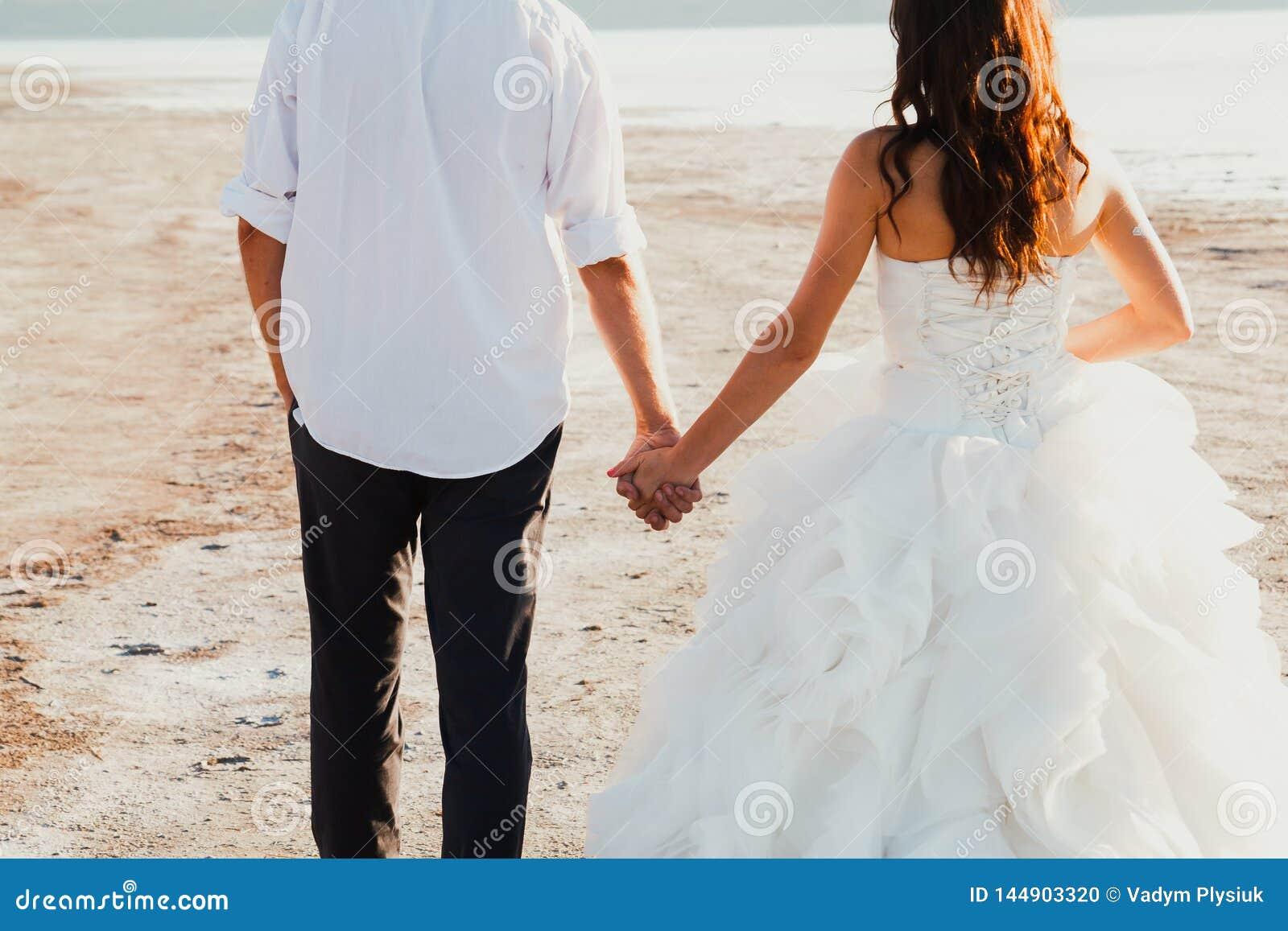 婚姻的夫妇在海海滩握手并且走开 晴朗的夏天照片 有头发的新娘下来在肩膀礼服