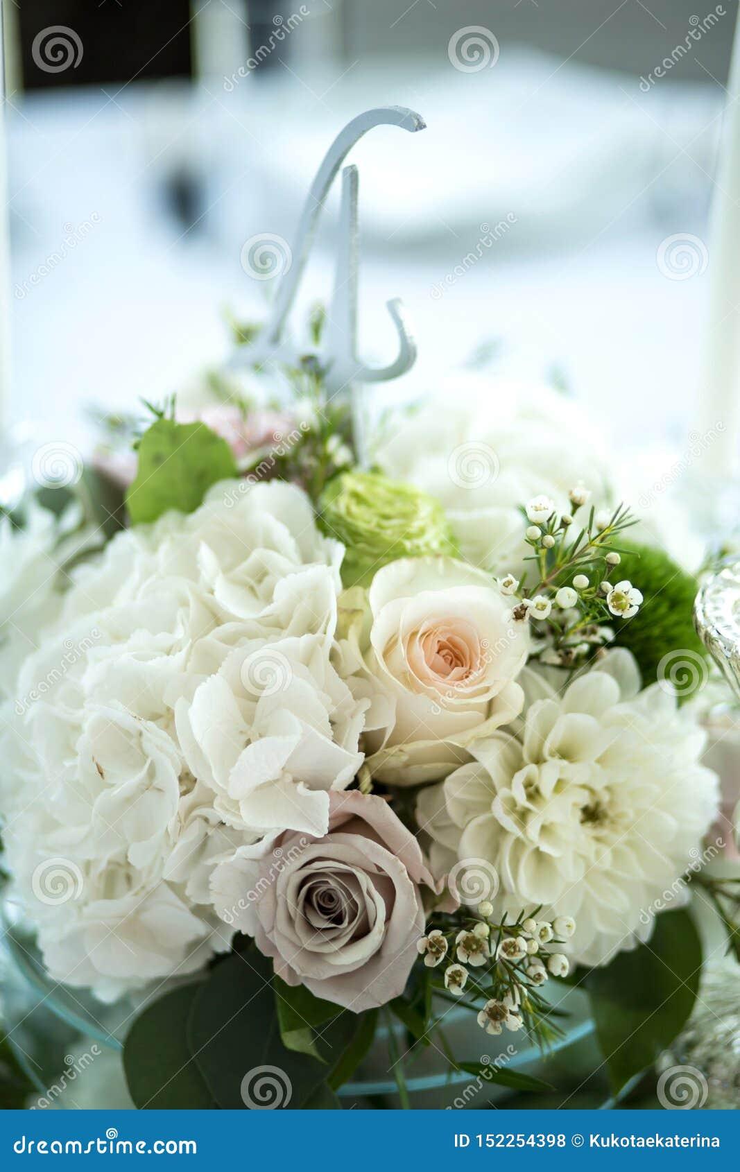 婚姻的桌设置用鲜花和白色蜡烛装饰 ??floristry 与玫瑰的花束,八仙花属和