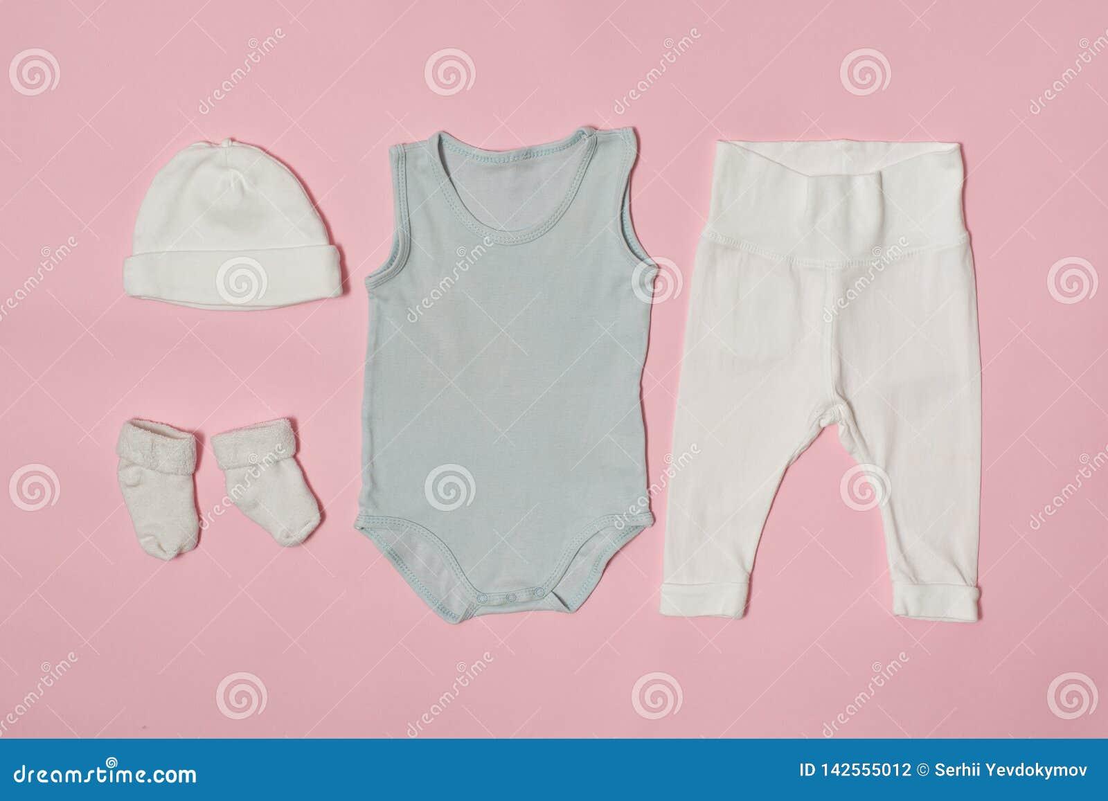 婴孩在桃红色背景的时尚概念 盖帽、紧身衣裤、裤子和袜子
