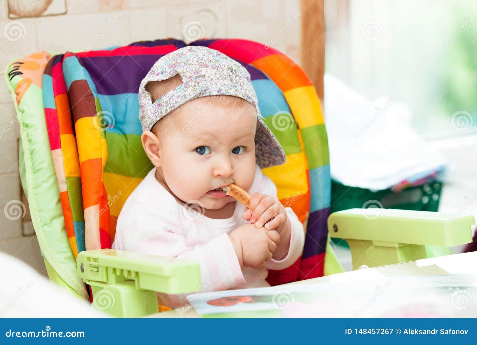 婴孩在高脚椅子坐并且吃