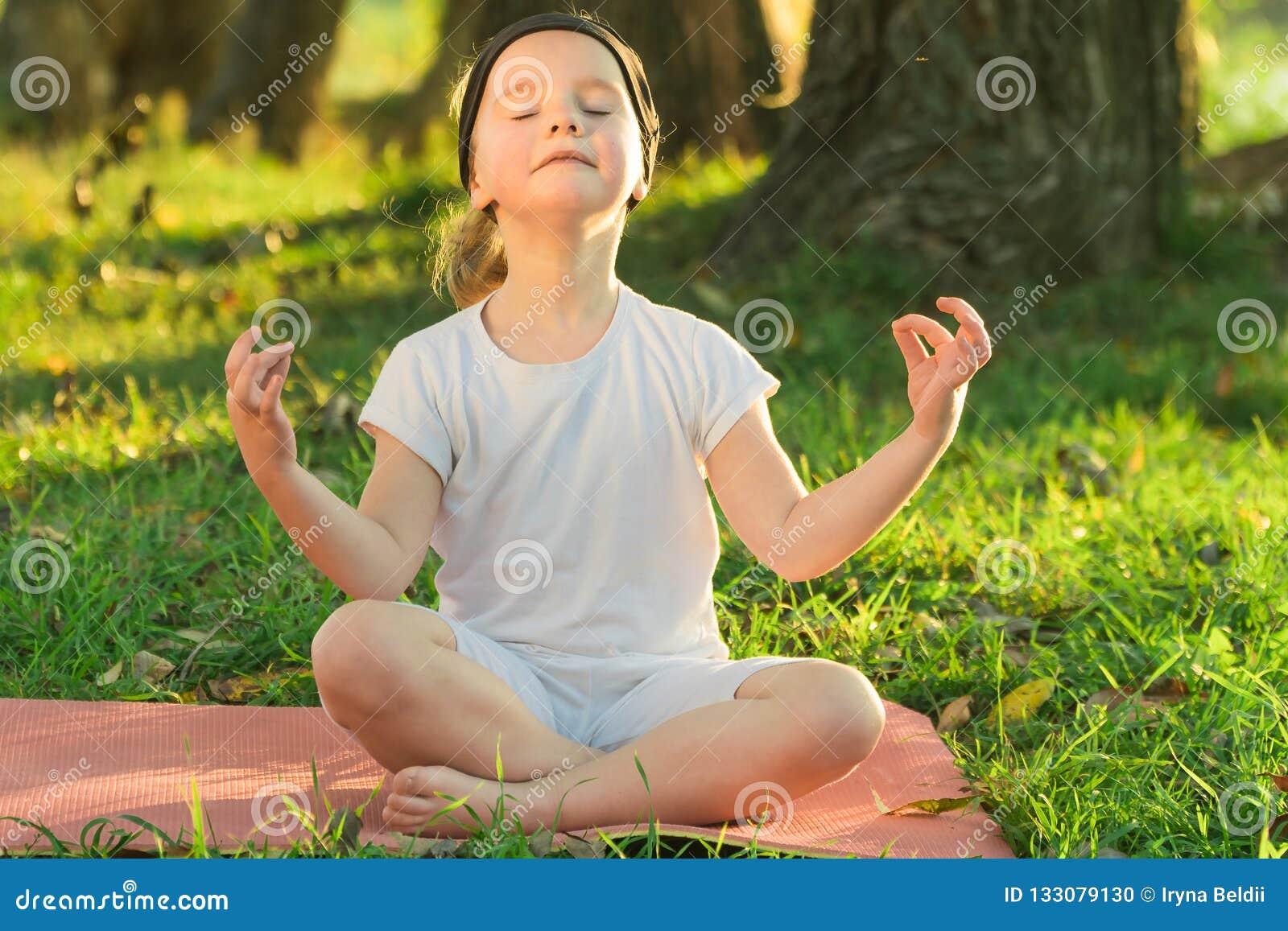 婴孩瑜伽莲花姿势 儿童实践的瑜伽户外