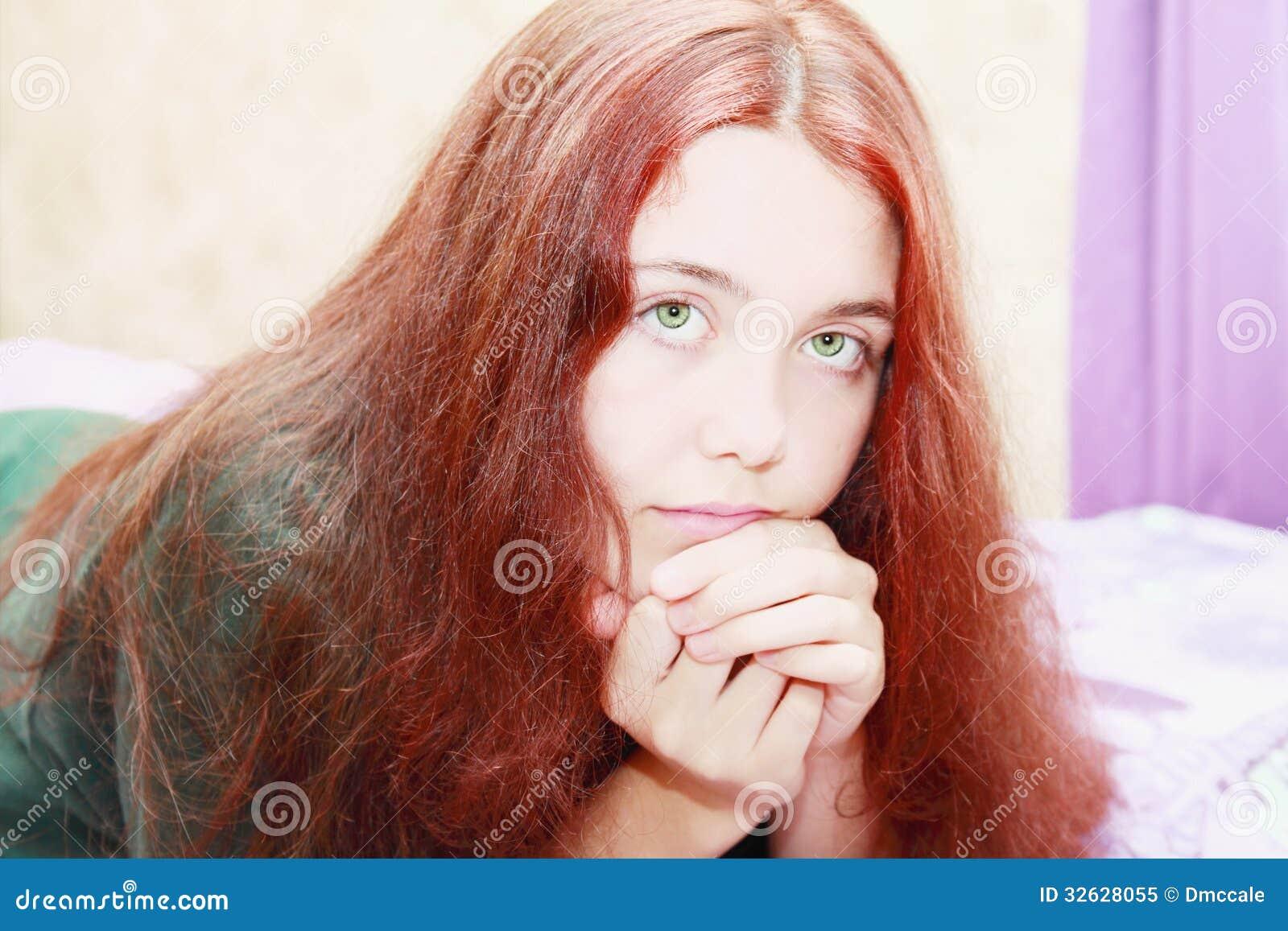 有长红色波浪发微笑的美丽的青少年的女孩.图片