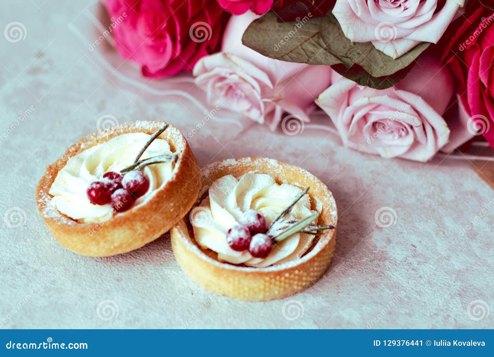 嫩浪漫礼物:甜点结块与奶油和莓果和桃红色玫瑰花束在轻的背景