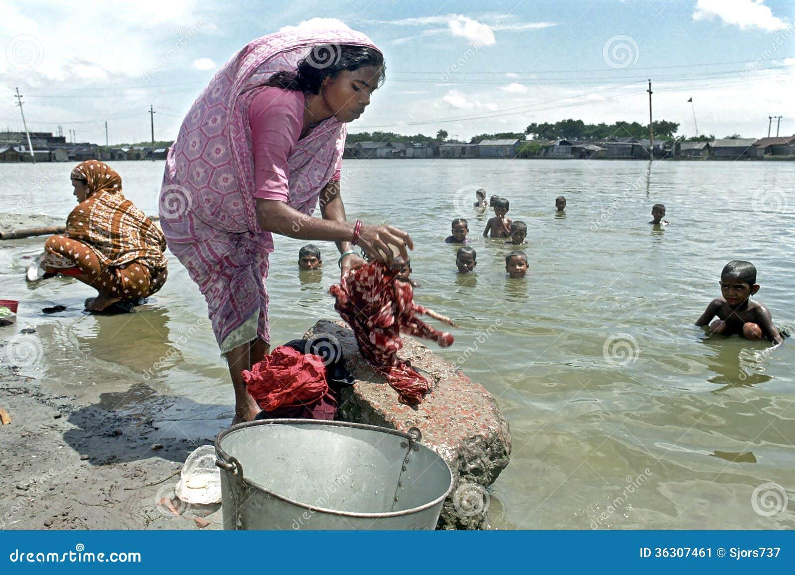 孟加拉国的妇女洗涤的衣裳在湖