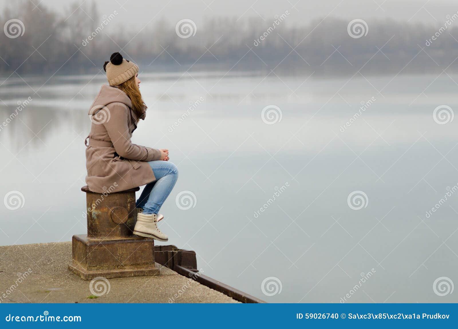 孤独的哀伤的十几岁的女孩坐船坞在冷的冬日