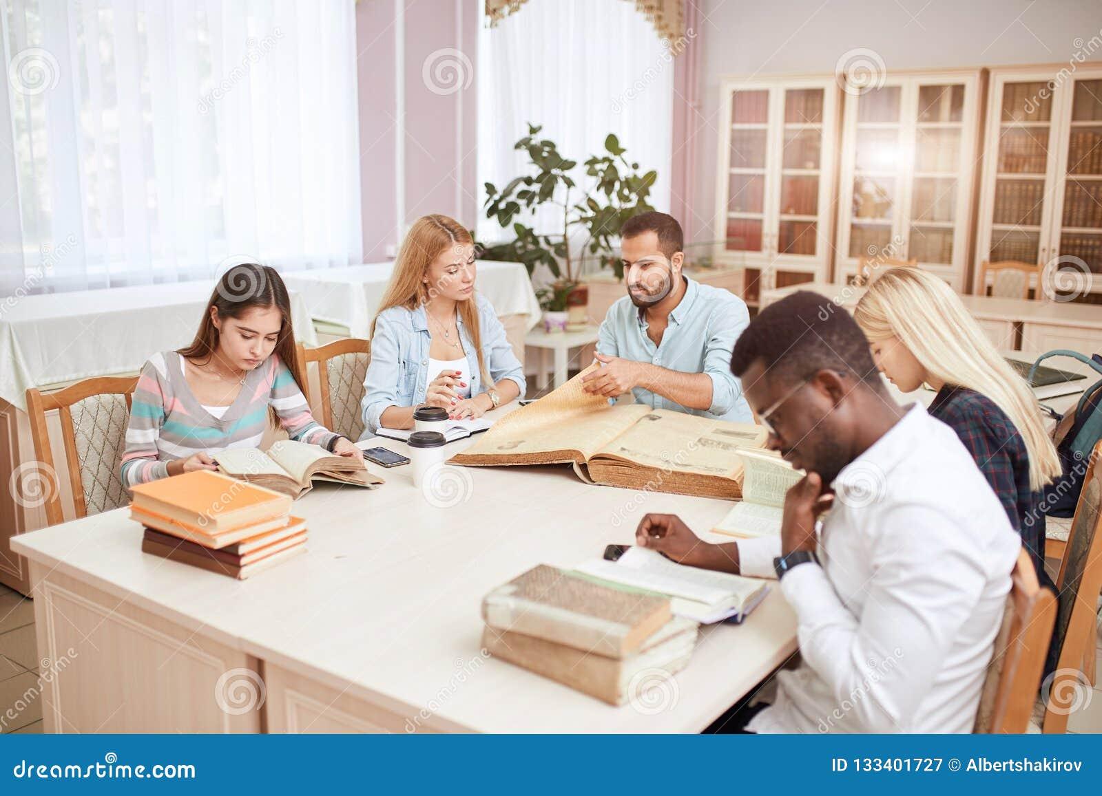 学习与书的小组多种族人民在大学图书馆里