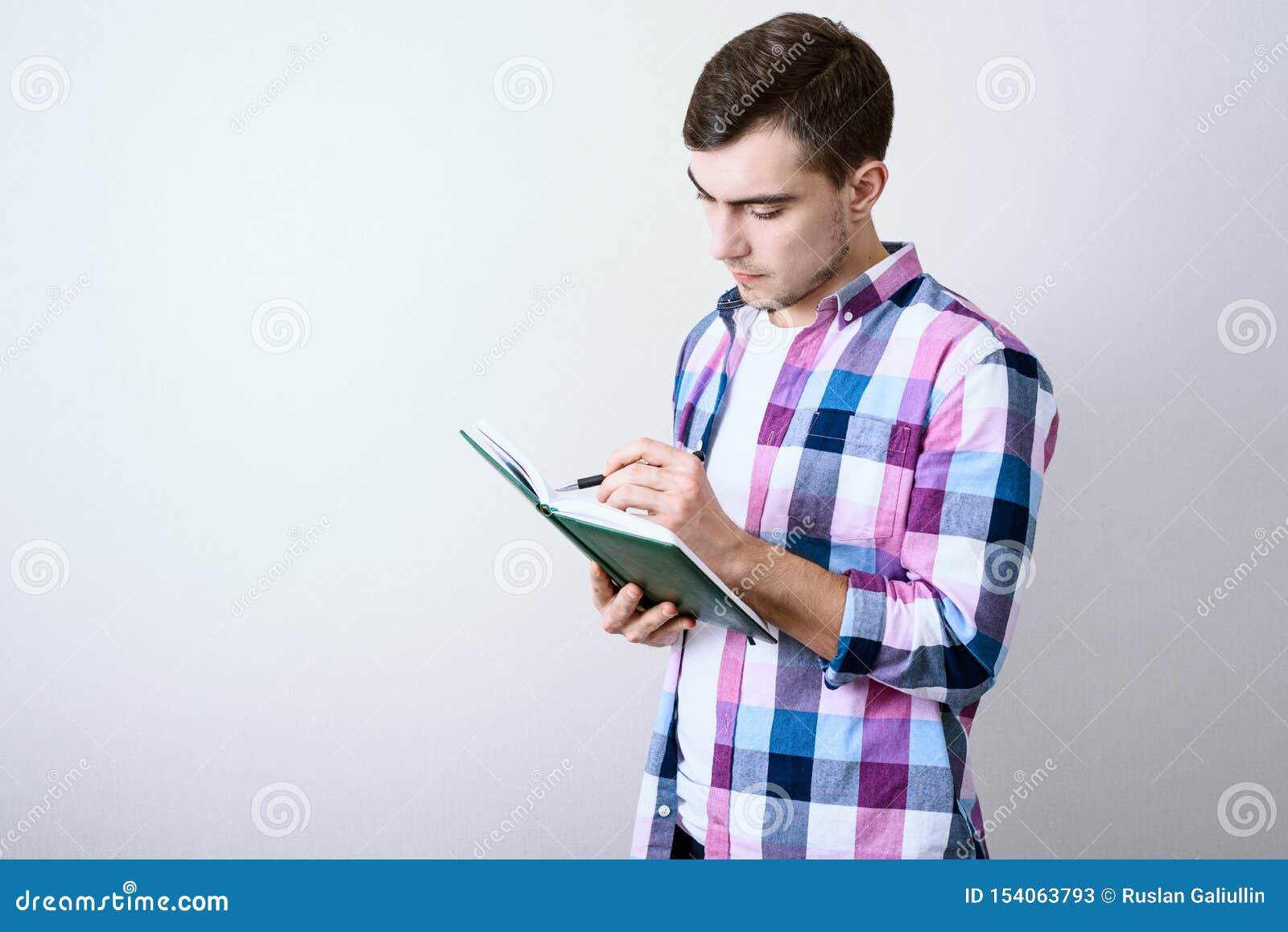 学习关于灰色背景的年轻白男生演讲笔记与拷贝空间