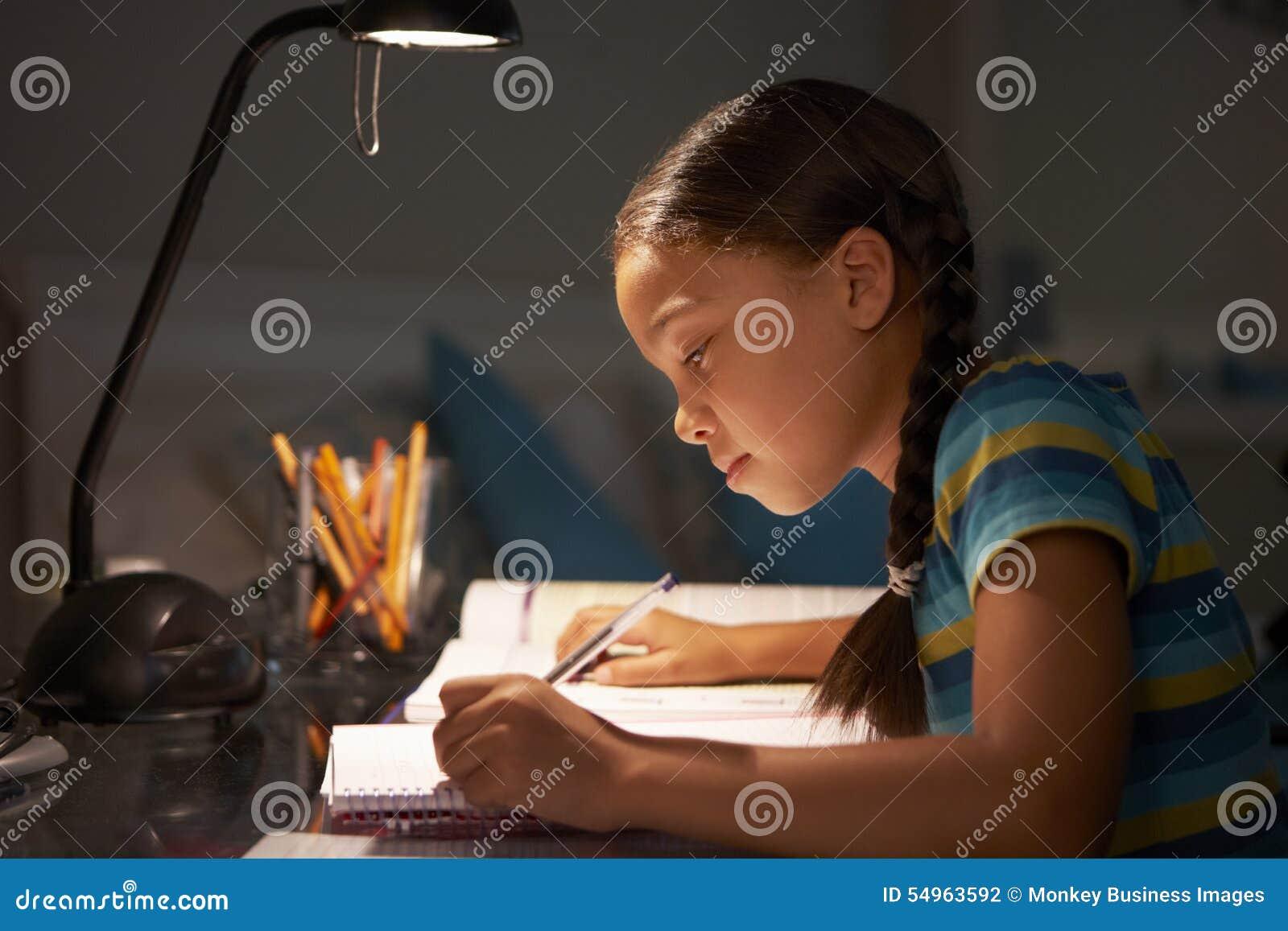 学习在书桌的女孩在卧室在晚上
