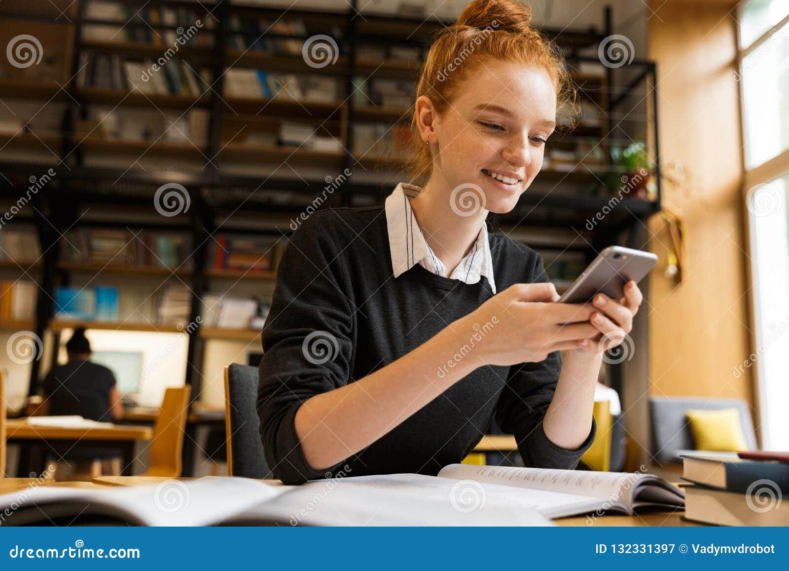 学习在桌上的微笑的红发十几岁的女孩