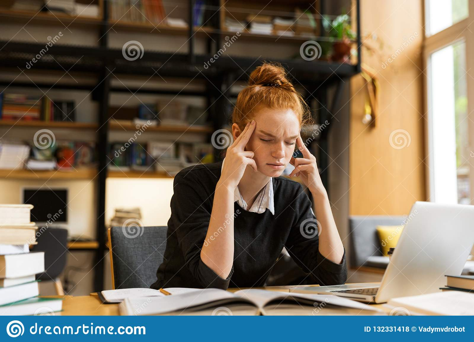 学习紧张的被集中的妇女的图象,当坐在des时