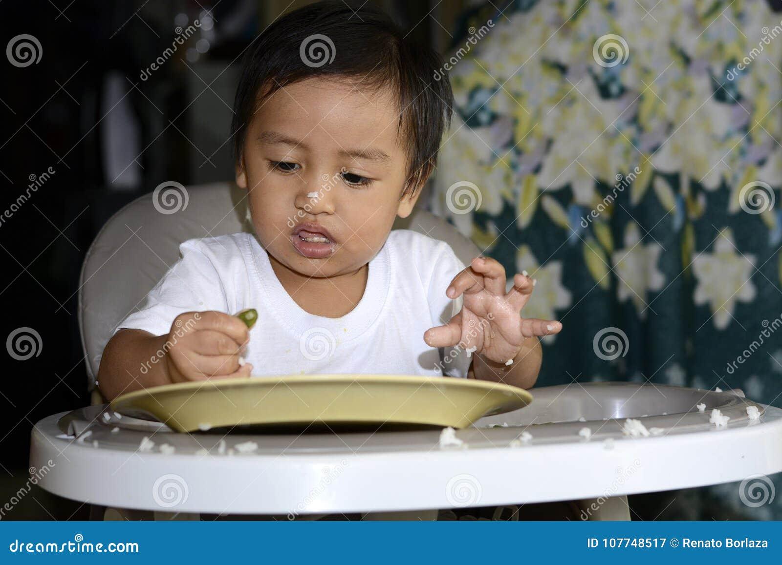 学会一1岁亚裔的男婴由匙子吃他自己,杂乱在用餐椅子的婴孩