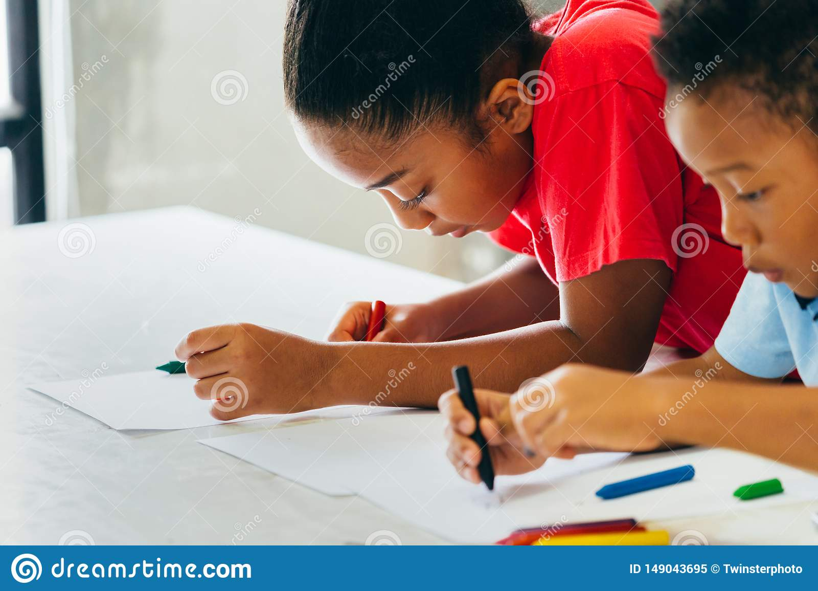 学会如何的非裔美国人的孩子画与在桌上的蜡笔
