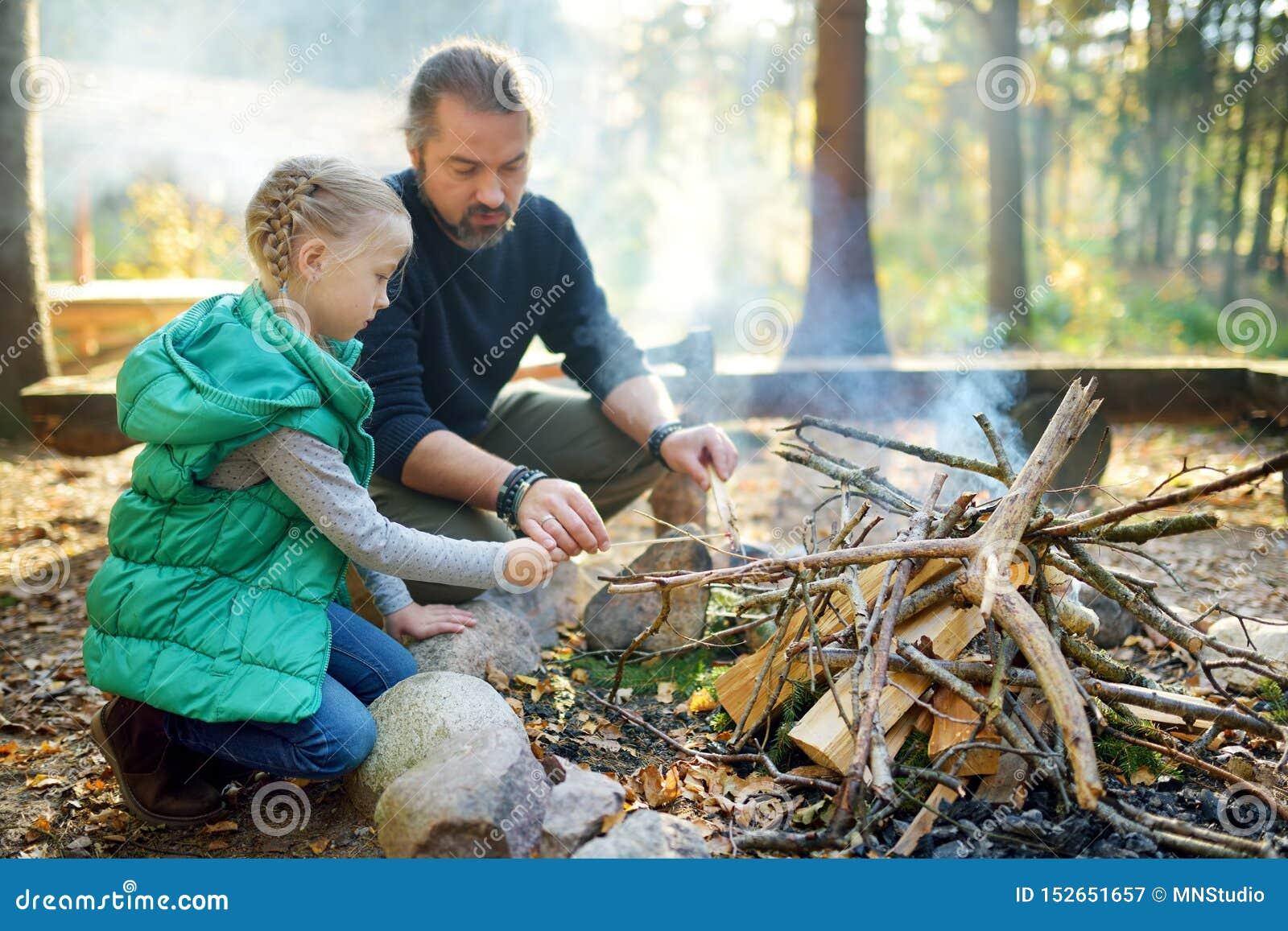 学会逗人喜爱的少女开始篝火 教她的女儿的父亲做火 孩子获得乐趣在阵营火 ??