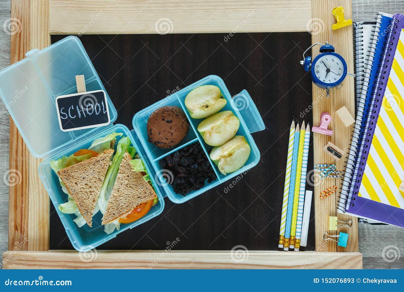 学校蓝色饭盒用自创三明治,绿色苹果,曲奇饼,铅笔,时钟,在桌上的笔记本 E